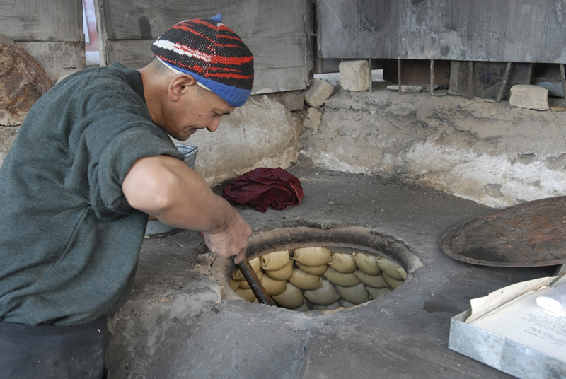 A baker cooks naan, in a traditional tandyr, a style of clay, wood-fired oven used for centuries.